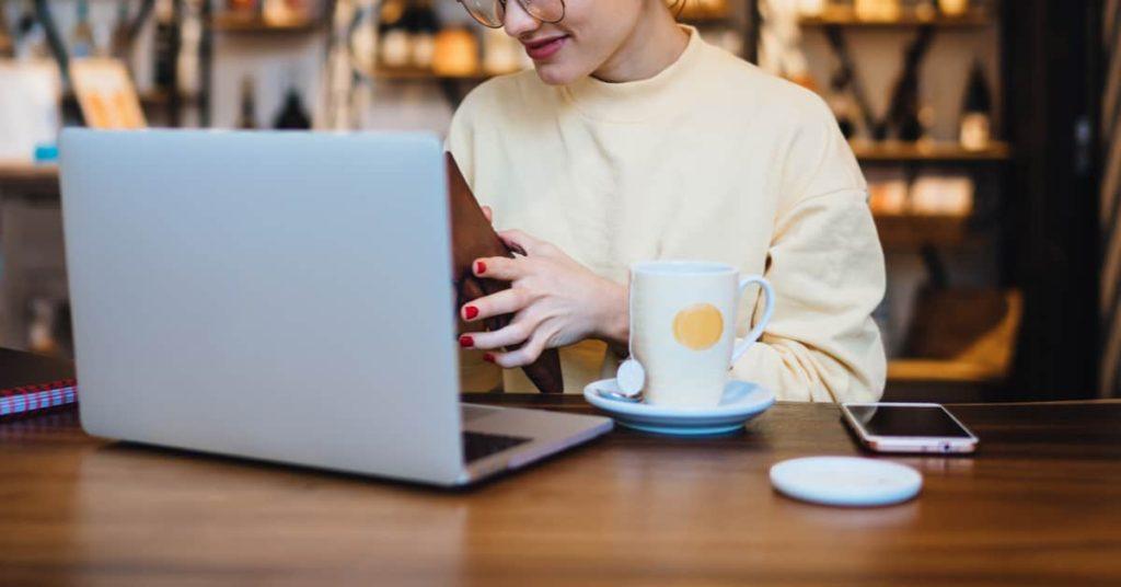 カフェでパソコンを使用して動画配信サイトでアニメを見る女性