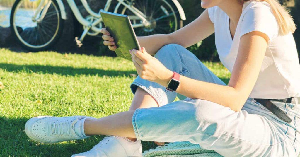 芝生に座ってタブレットでアニメを見る女性